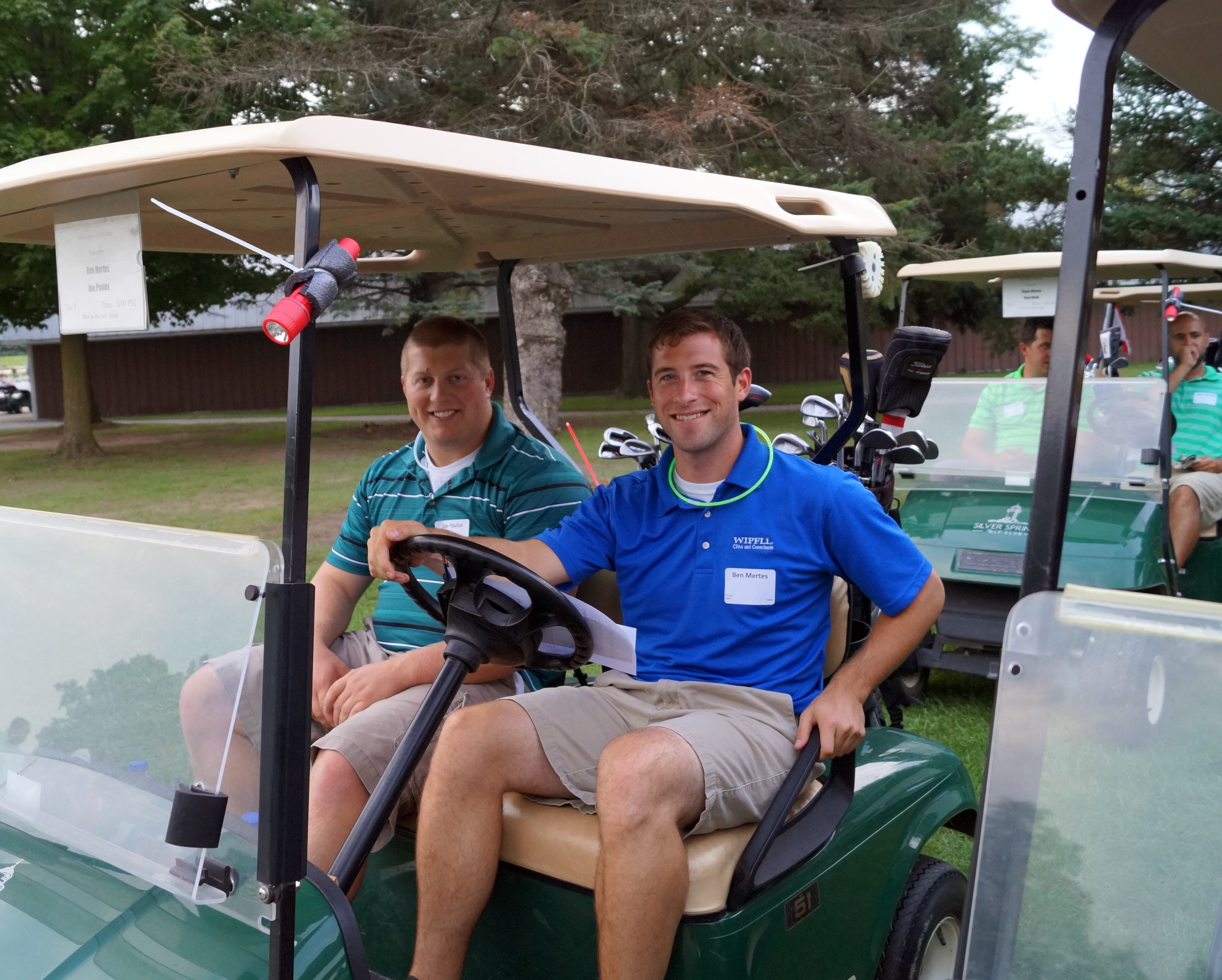 Two young men are very happily sitting in a golf cart.