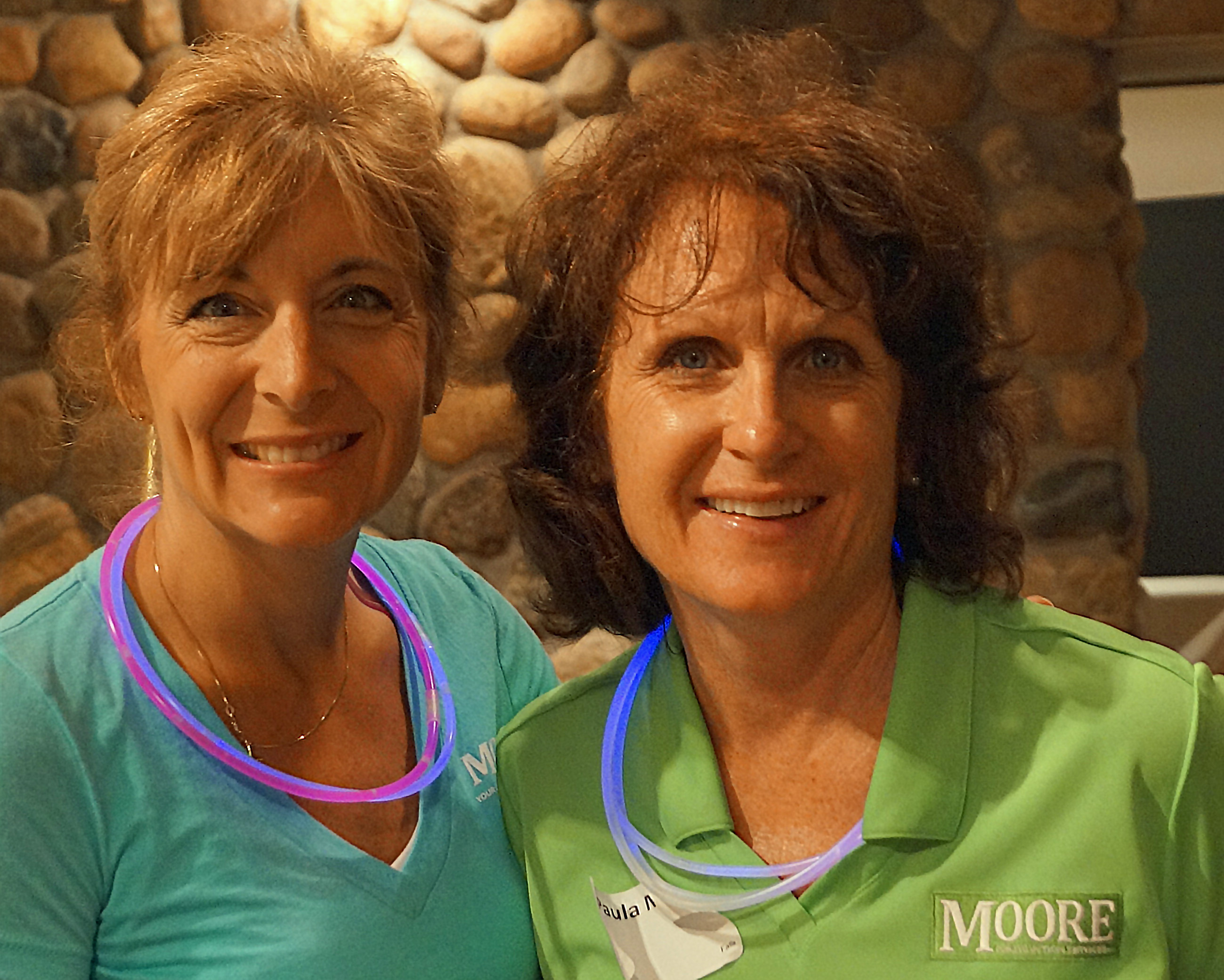 Two women are smiling brightly and wearing glow in the dark necklaces.