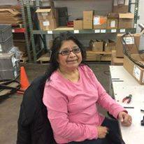 Sophia sits at a work desk with some tools and shelves with boxes behind her. She is wearing a pinks shirt and dark glasses with a friendly smile.